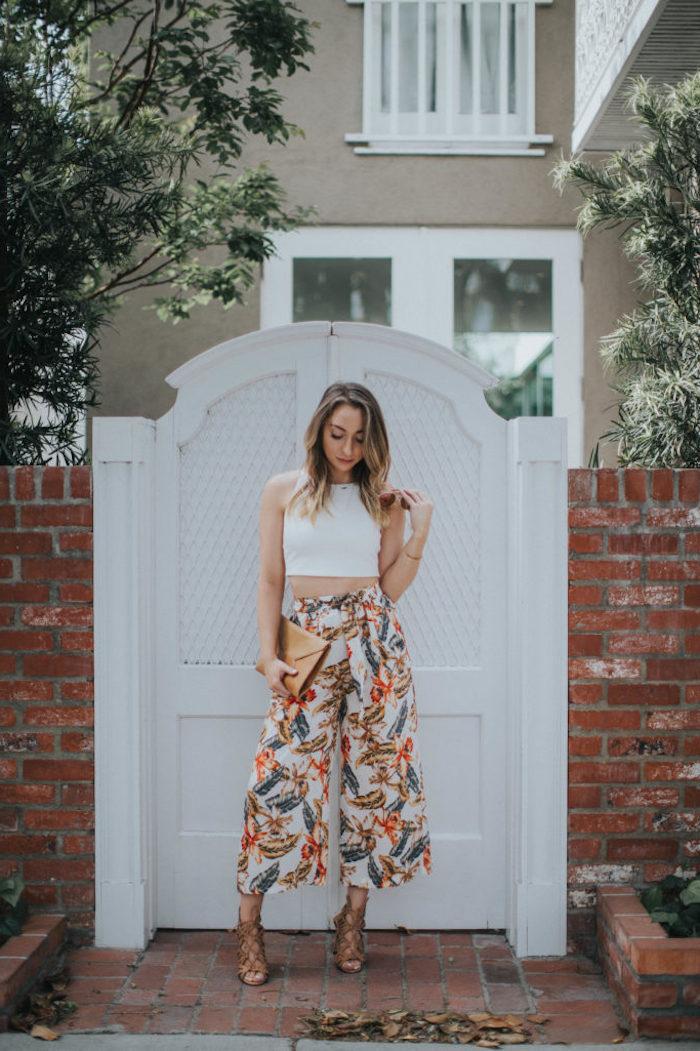 elegantes outfit culotte hose kombinieren weite hose mit bunte blumen abdruck weißes crop top braune haare mit blonden strähnen casual chic outfit