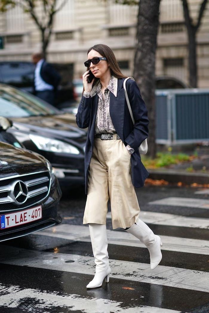 fashion week street style beige hose kombiniren mit weißen stiefeln dunklem trenchcoat und gemusterte bluse fraun mit langen braunen haaren