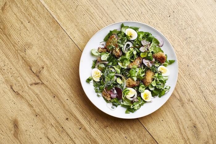 feldsalat dressing ein tisch aus holz weier teller mit salat mit eiern und brot