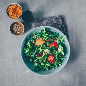 feldsalat rezept eine graue schüssel mit salat mit grünem feldsalat und tomaten kurkuma und pfeffer feldsalat dressing