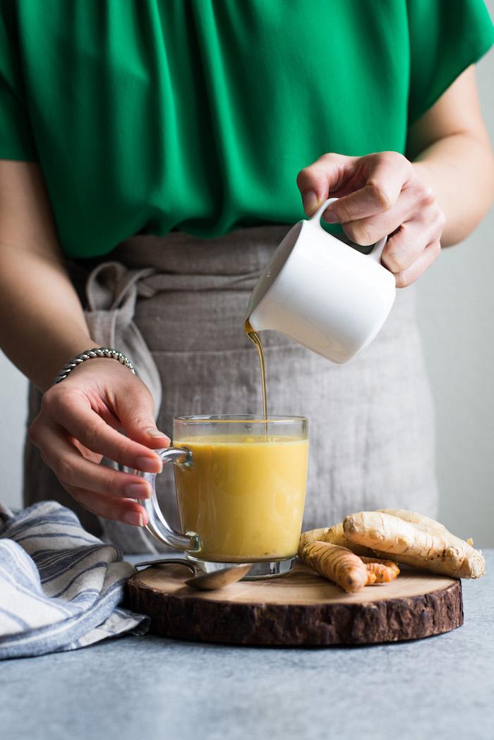 frau mit einem glas mit goldener milch ein holzbrett vegane goldene milch rezept ingwer und kurkuma