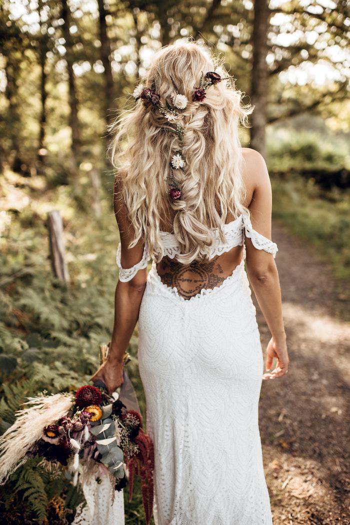 frau-mit-tattoos-auf-dem-rücken-flechtfrisuren-halboffen-enges-weißes-hochzeitskleid-ohne-rücken-lange-blonde-haare-mit-locken-kleine-blumen-im-haar