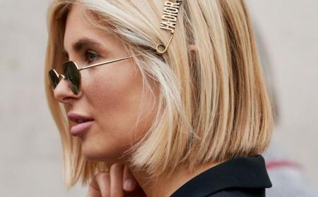 frisur für glatte schulterlange haare mit haarsprangen blonde frau xenia adonts mit schwarzen sonnenbrillen und schwarzem sakko auf hellem hintergrund