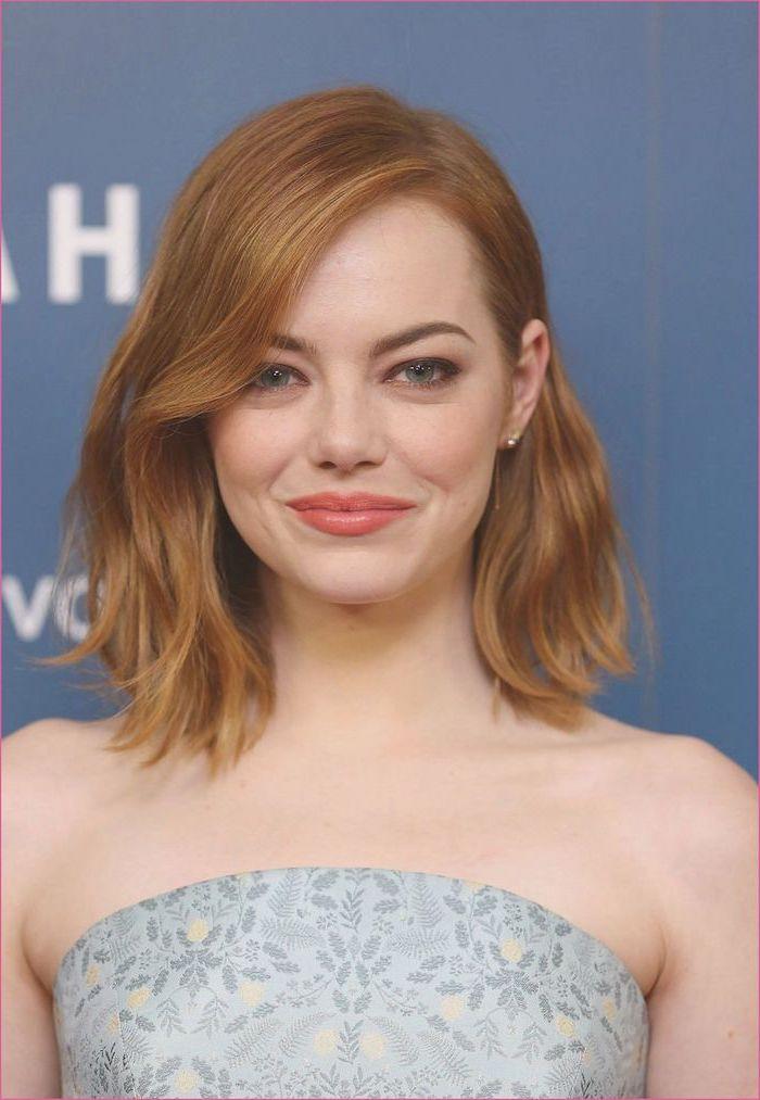 frisur für schulterlanges welliges haar auf stufen emma stone elegant auch für den alltag graues kleid mit hellen blumen
