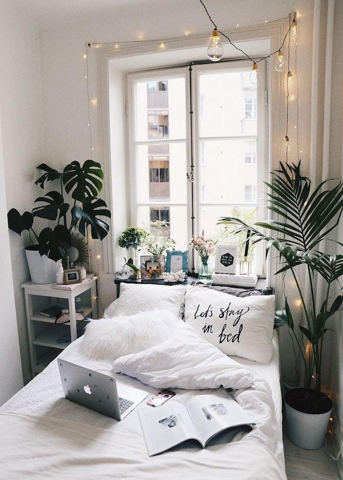 gemütliches kleines schlafzimmer design dekoration grüne pflanzen weißer kissen mit abdruck teenager zimmer mädchen dekorierte fensterbank aufgehängte lichterketten