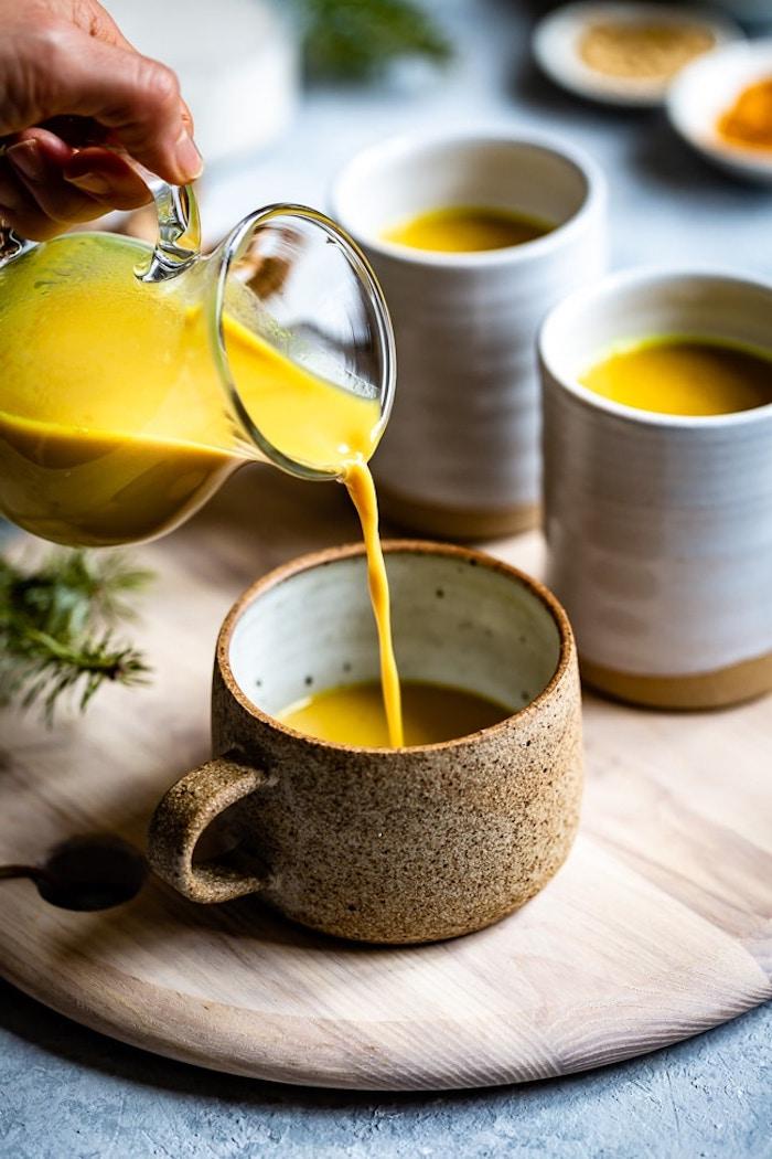 goldene milch mit kurkuma ingwer und kokosöl ein holzbrett weiße tassen die zutaten für vegane goldene milch