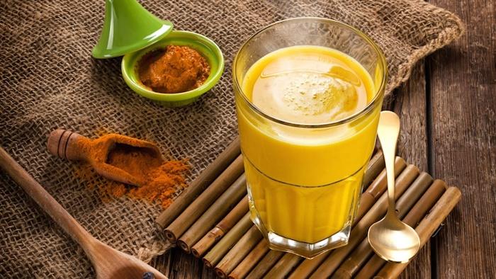 goldene milch nebenwirkung ein glas mit goldener gelber milch zimt und ingwer die zutaten für eine tasse goldene milch