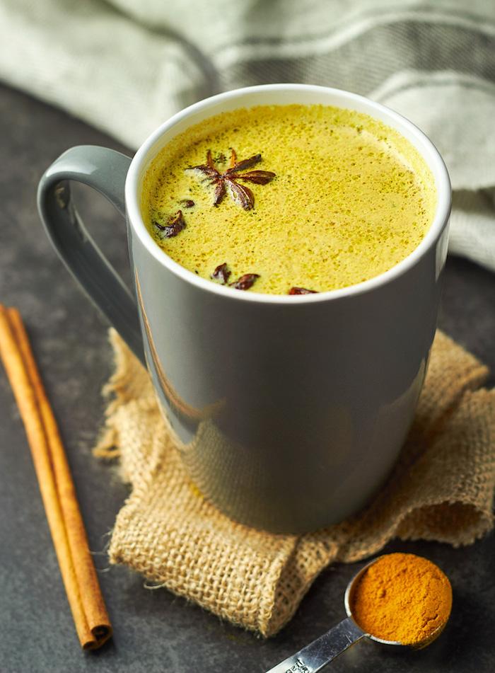 graue tasse mit goldener milch ein löffel mit zimt und kurkuma vegane goldene milch rezept