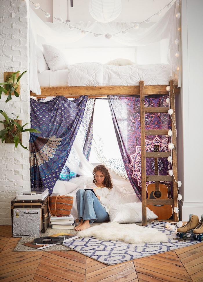 hippie style inneneinrichtung hochbett jugendzimmer mit leiter geometrischer teppich boho chic inneneinrichtung junges mädchen schreibt im heft bunte bettvorhänge