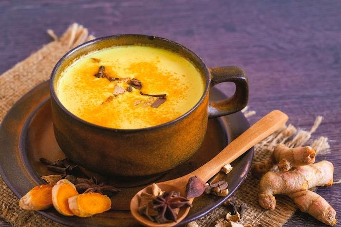 ingwer und zimt ein löffel aus holz eine braune tasse mit gelber goldener milch aus kurkuma milch ingwer und kokosöl