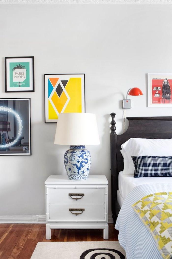kleines zimmer einrichten weißer nachttisch vintage lampe blau wandgestaltung jugenzimmer buntes gemälde kleine und große bilder an die wand großes bett brauner holzrahmen