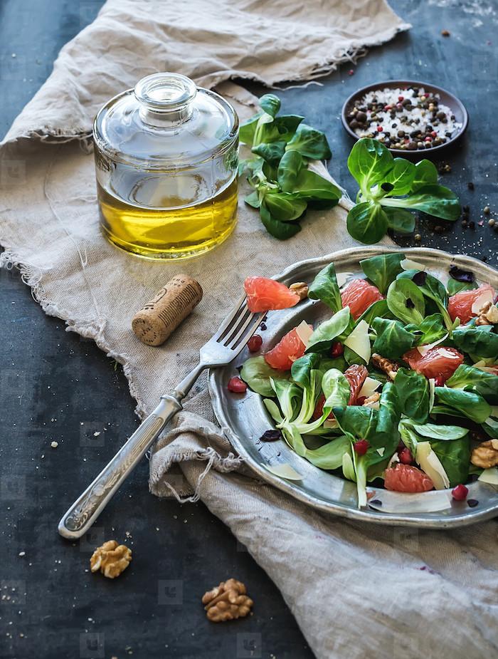 löffel und ein teller mit feldsalat die zutaten für salat mit feldsalat nüssen eine weiße decke ist feldsalat gesund