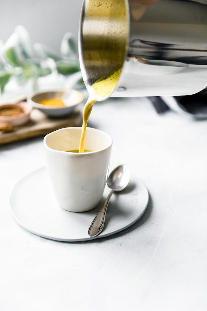 löffel und eine weiße tasse mit goldener milch vegane goldene milch rezept zubereitung