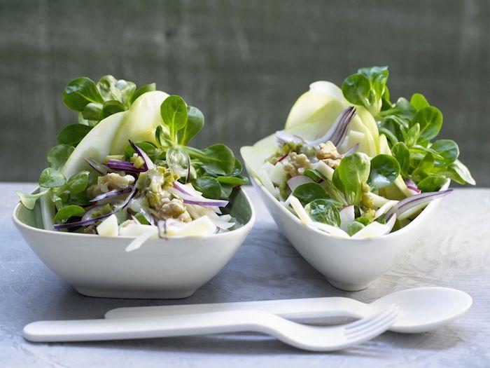 löffel und gabel aus plastik zwei weiße schüssel mit salaten mit grünen blättern eines feldsalats dressing für feldsalat