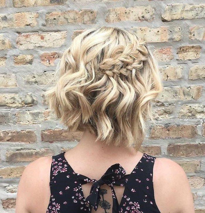 lockige frisur frau mit mittellangem haarschnitt blond mit seitenzopf schwarzes klied mit rosa blumen