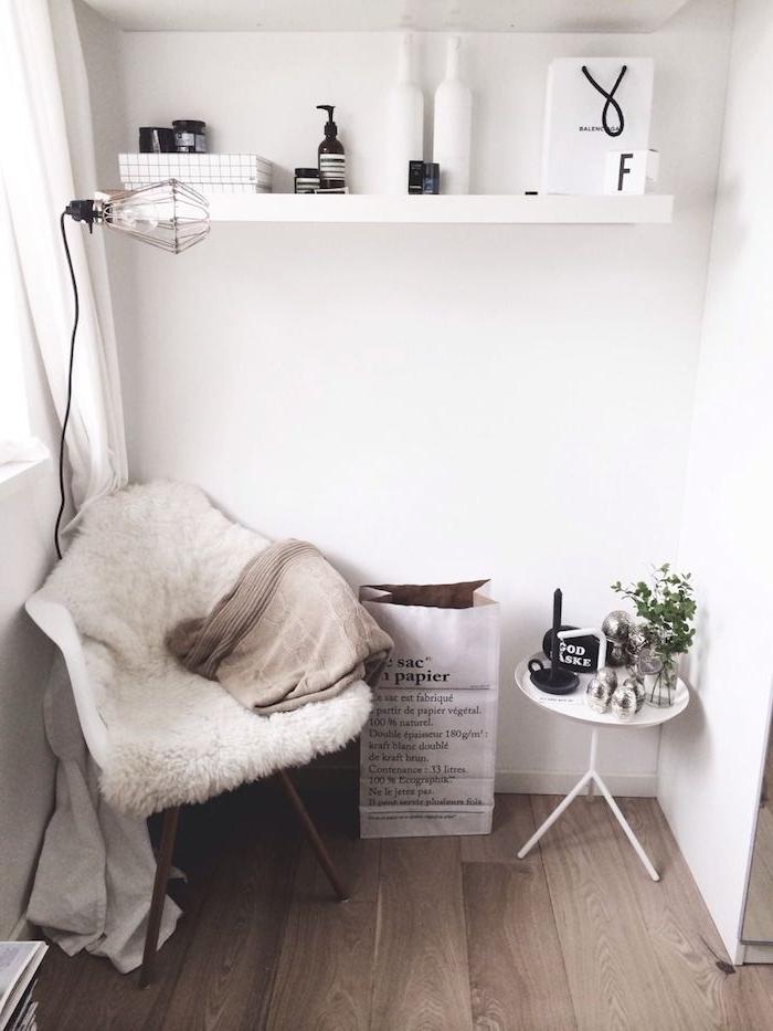 minimalistische inneneinrichtung weiß dekoartikel wohnzimmer offene regale stuhl mit flauschiger decke kleiner runder tisch industrial chic lampe