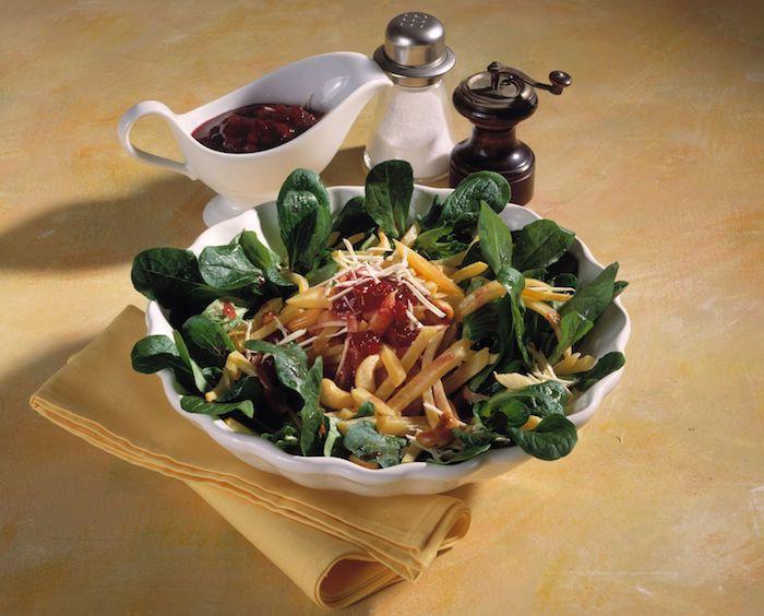 pfeffer und salz eine weiße schüssel mit salat mit käse tomatensauce und mit grünne blettern eines feldsalats
