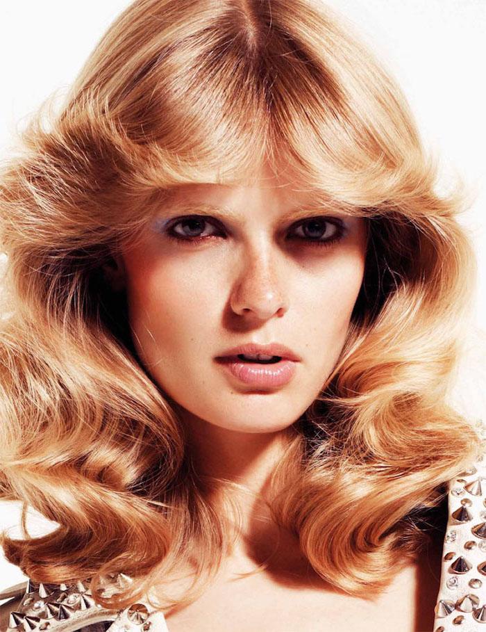 retro frisur aus den 70 er frau mit mittellangem welligen haar blond auf weißem hintergrund