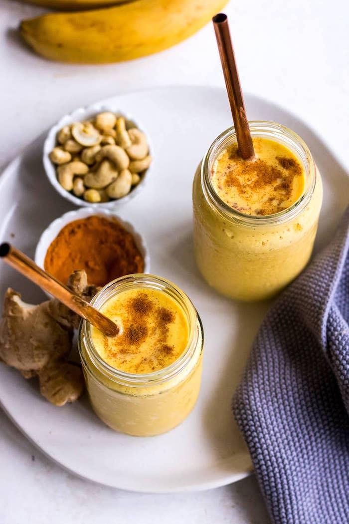 rezept für goldene milch drei gläser mit goldener milch mit zimt ingwer eine blaue decke weißer teller