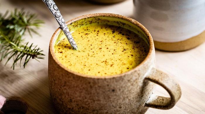 rezept für goldene milch eine tasse mit löffel und asiatischem getränk ein brett aus holz vegane goldene milch