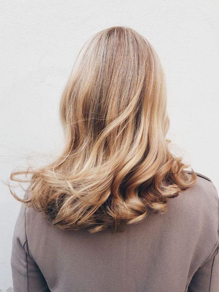 schöne frisuren für schulterlange haare blondes haar frau mit hellbraunem pulli auf weißem hintergrund