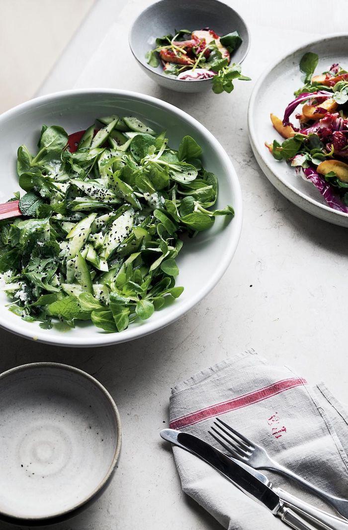 schüssel mit grünen blättern eines feldsalats mit pfeffer und dressinh messer und gabel weißer tisch feldsalat rezept