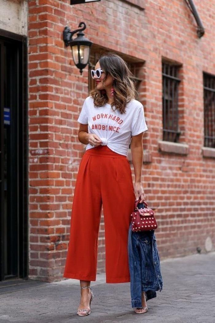 stylisches outfit rote collot hose in rot weißes t shirt mit print kurzhaarfrisuren braune haare mit blonden strähne weiße sonnenbrillen jeansjacke schuhe mit absatz und weite hose