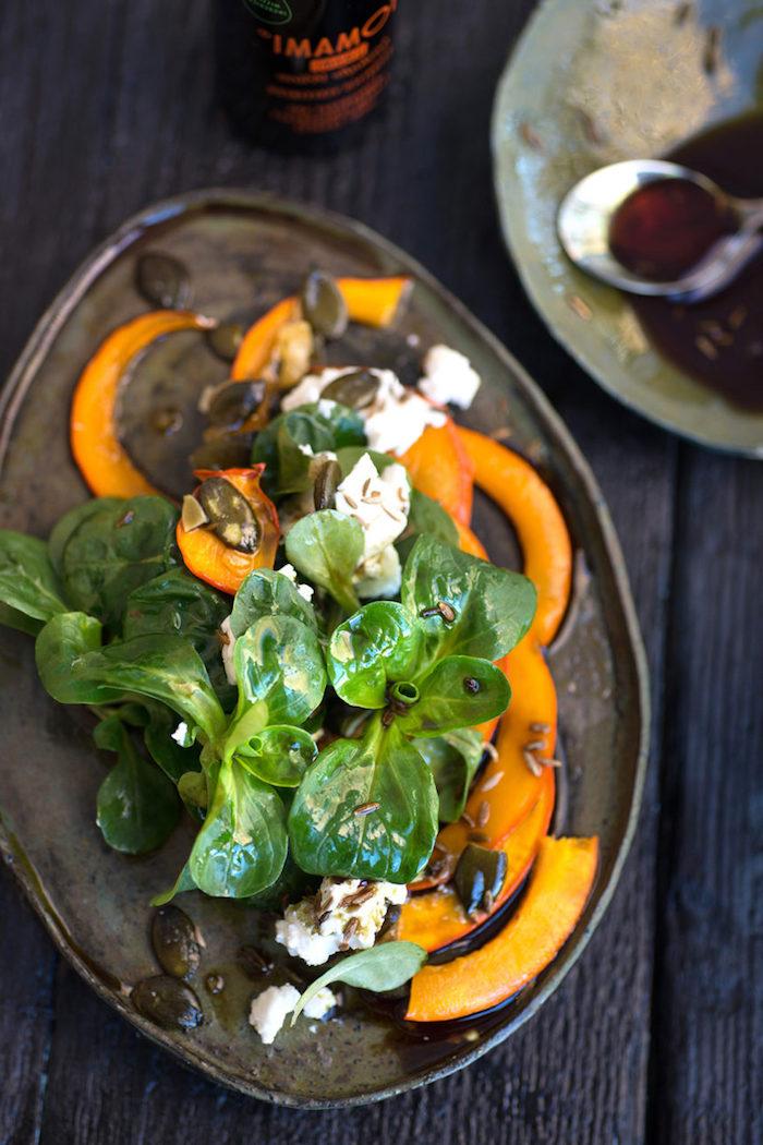 teller ein salat mit käse und grünen blättern eines feldsalats dressing für feldsalat schwarzer tisch aus holz ein löffel