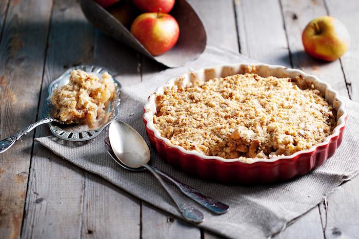 tisch aus holz teller mit apple crumble löffel rote äpfel knuspriges apple crumble rezept