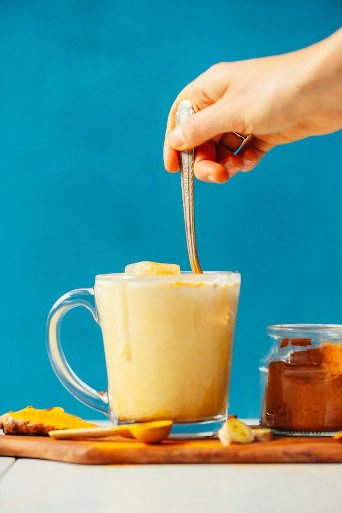 vegane goldene milch rezept ein glas mit gelber milch eine hand mit löffe ein glas mit kurkuma