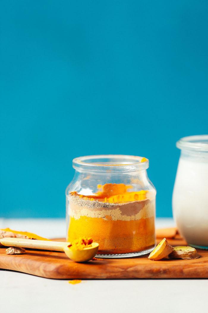 vegane goldene milch rezept ein löffel aus holz ein brett aus holz die zuatten für ein glas mit goldene milch