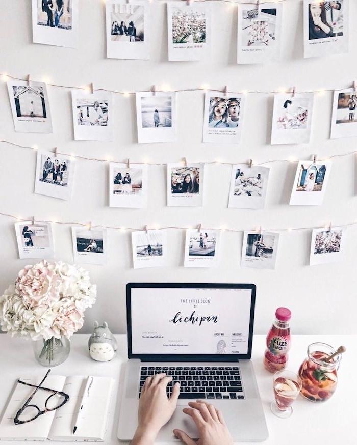 wand mit vielen aufgehängten fotos person arbeitet am computer vase mit schönen weißen blumen zimmer tumblr einrichten modern