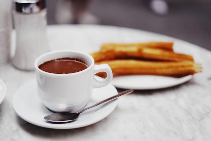 weiße tasse mit kaffee was kann man heute machen ein teller mit langen gelben churros seler machen