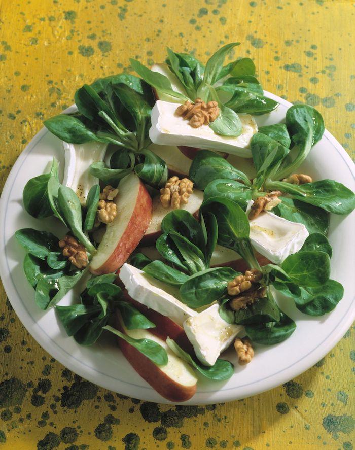 weißer teller mit salat mit frischen walnüssen geschnittenen äpfeln und grünen blättern eines feldsalats