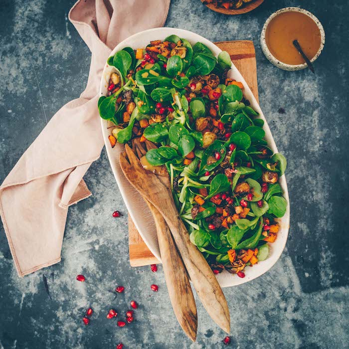 weißer teller mit salat mit grünen blättern eines feldsalats löffel ais holz eine weiße decle blauer tisch feldsalat rezept