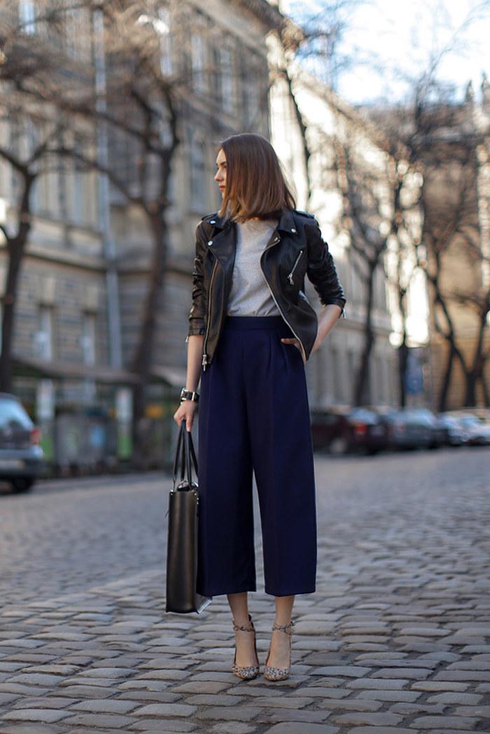 weite blaue collot hose gestylet mit grauem t shirt lederjakcke und großer schwarzer tasche street style ideen und inspiration kurzhaarfrisuren schuhe mit absatz