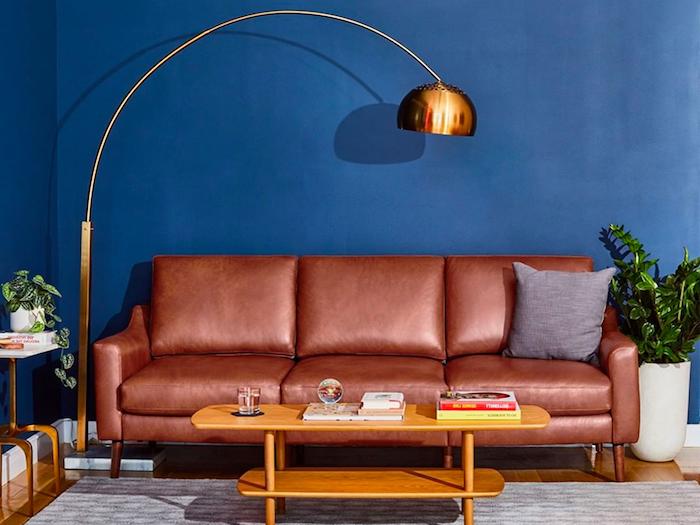 wohnzimmerwand ideen wand in marineblau mit sofa aus leder kombinieren lampe kupferfarbig