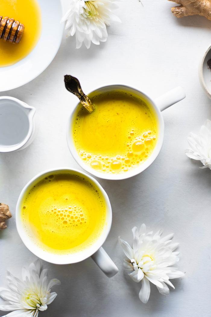 zwei weiße tassen mit gelber goldener milch nebenwirkungen tisch mit vielen weißen blumen