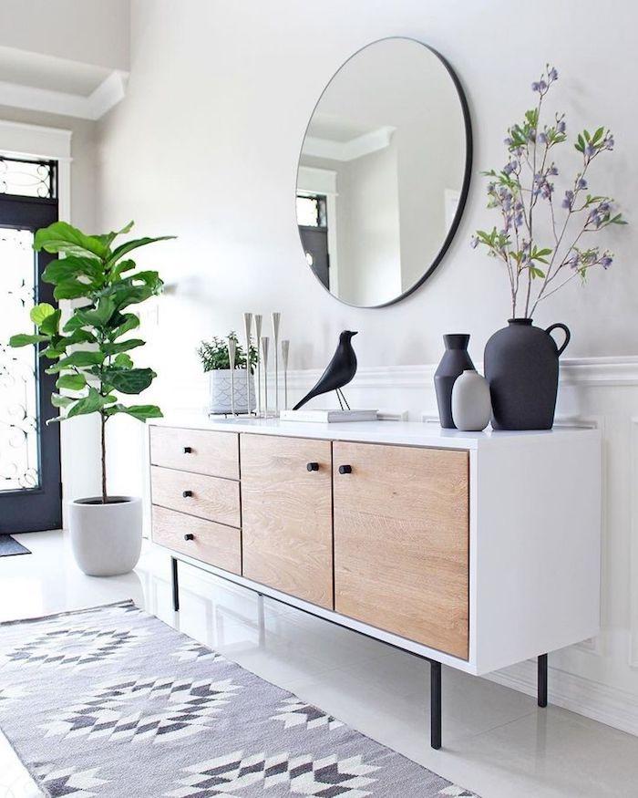 5 minimalistische inneneinrichtung weiße kommode türe aus holz geometrischer teppich skandinavische deko figuren schwarzer vogel vasen weißer topf grüne pflanze runder spiegel