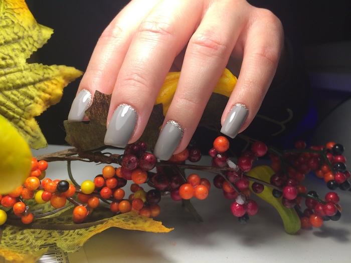 ast mit vielen kleinen orangen früchten eine hand mit beigem nagellack große gelbe blätter im herbst