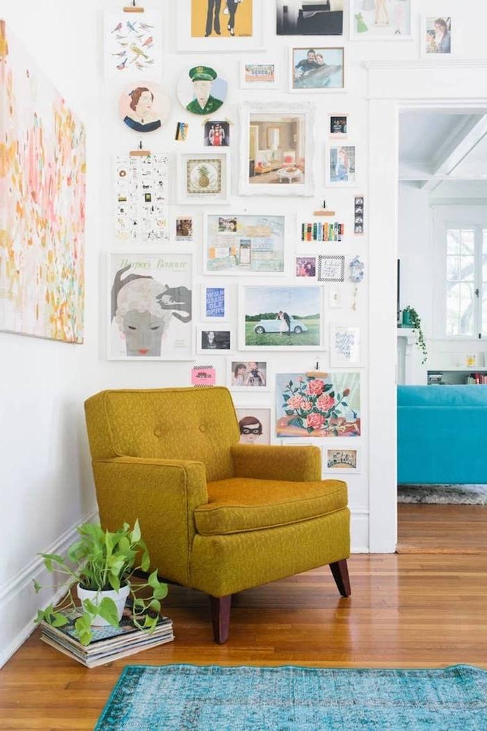 bilderwand gestalten kleine und große zeichnungen blauer teppich senffarbener sessel wohnzimmerwand ideen abstraktes buntes gemälde