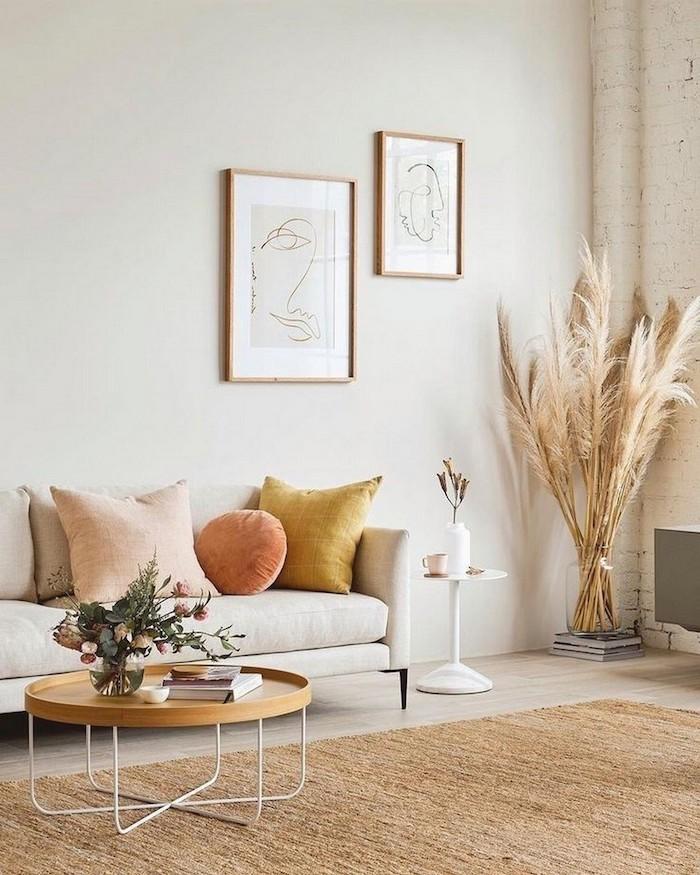 böhmischer stil inneneinrichtung boho chic linienzeichnungen wanddeko neutrale farbtöne gelbe und blassrosa kissen runder holztisch mit metallbeinen wohnzimmer einrichten modern