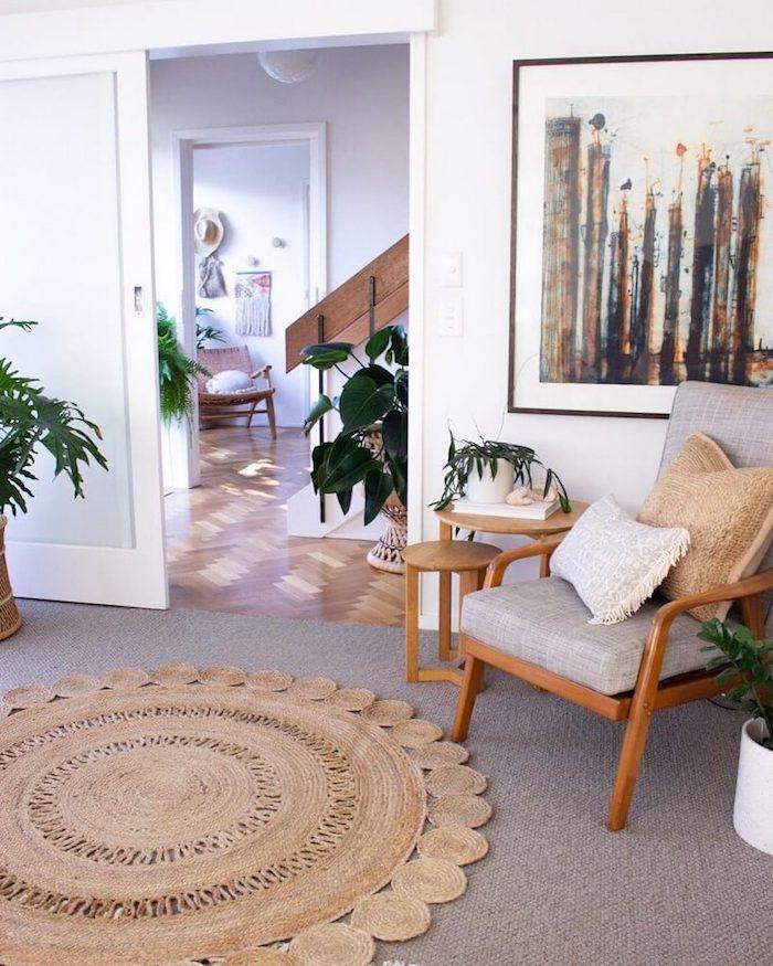 boho chic inneneinrichtung runder teppich großes abstraktes gemälde holzstuhl graue poslterung grüne pflanzen dekoration holzakzente möbel