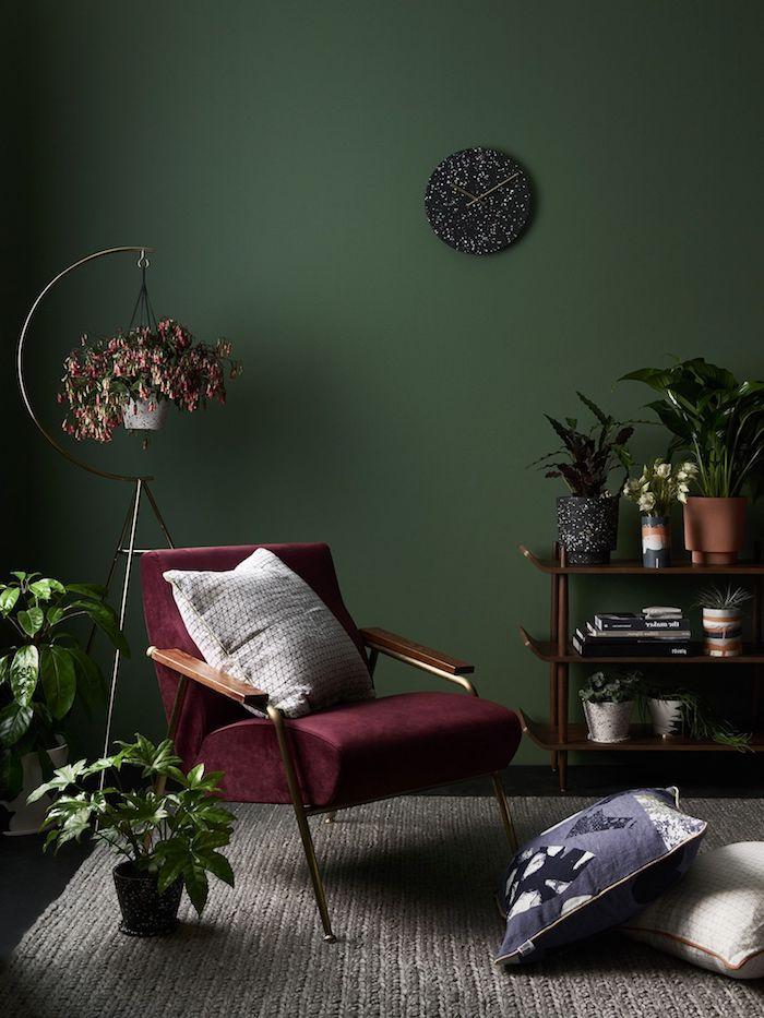 burgundfarbener stuhl weißes kissen wandfarbe grün deko wohnzimmer modern viele pflanzen und blumen schwarze runde wanduhr moderne inneneinrichtung