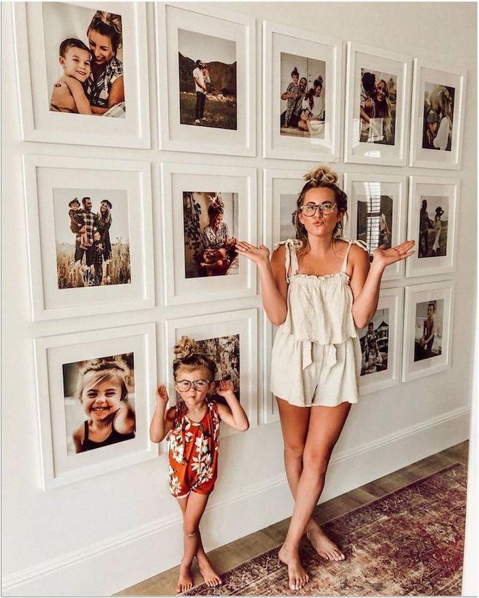 casual outfit frau im weißen kumper mutter und tochter vor fotowand familienfotos wanddeko wohnzimmer modern weiße wand mit fotos