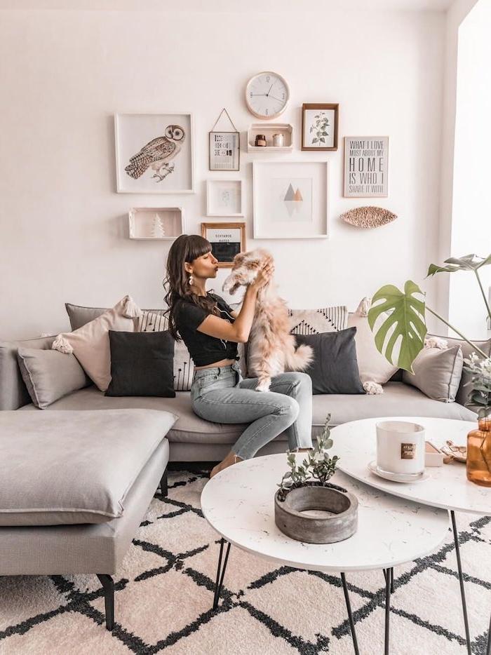 dame im casual outfit blaue jeans schwarzes t shirt braune haare hält einen hund ecksofa grau wohnzimmer einrichten wanddekoration bilder dekorative kissen grau pinke töne stilvolle deko für das wohnzimmer