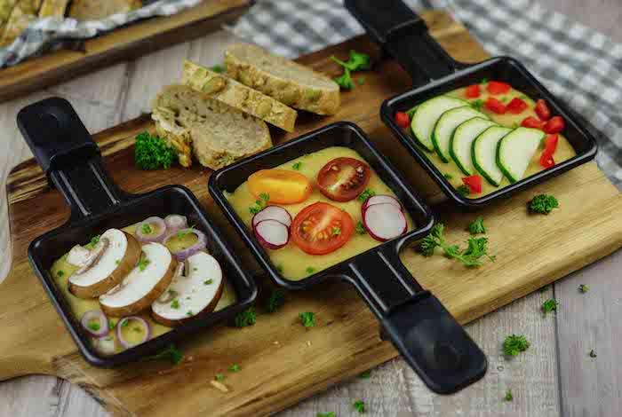 drei schwarze pfännachen mit raclette zutaten geschnittene champignons knoblauch und tomaten und gurken brot