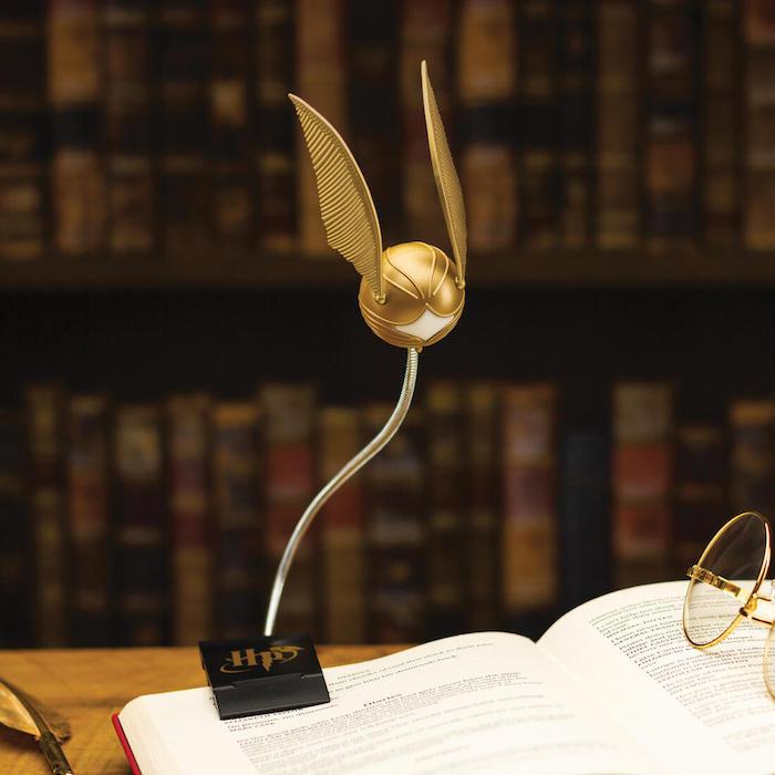 ein buch und brille eine kleine lampe mit einem goldenen snitch mit goldenen flügeln