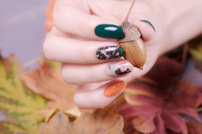 ein eichel und eine hand mit fingern mit einem nagellack für den hebst nageldesign herbst orange und dunkegrüne nägel
