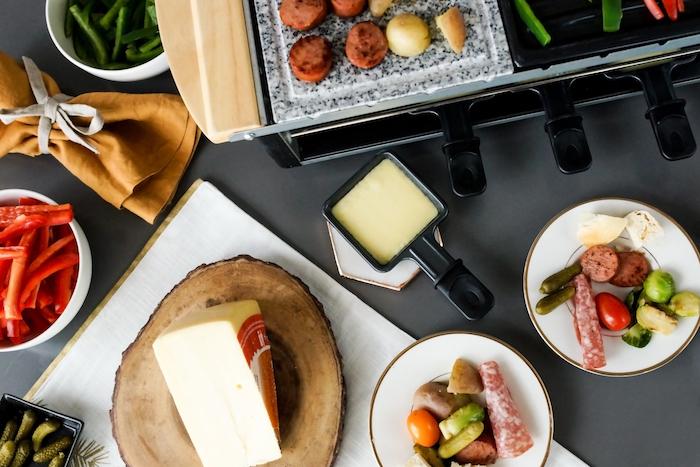 ein holzbrett mit käse eine schwarze pfanne mit gechmolzenem raclette käse schinken und gemüse rote paprikaschotten